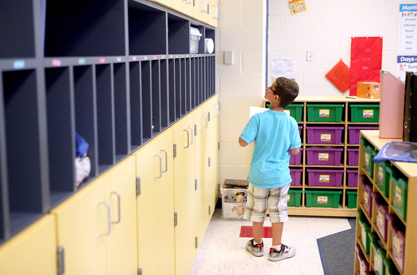 First-grader Devin Clesen searches for his cubby in his new classroom at Blackberry Creek Elementary School in Elburn during a supply drop-off session Monday afternoon.