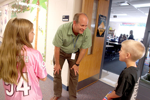 Blackberry Creek Elementary School third-grade teacher greets fourth-grader Alexis Nesci and second-grader Ryan Jones outside his classroom during a supply drop-off session at the Elburn school Monday afternoon.