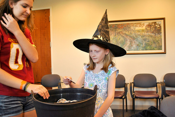 "Caroline Eichelberger (left) helps Amber Painer (9), both of Elburn, get ""sorted"" at the Town and Country Public Library's birthday party for Harry Potter Tuesday afternoon."