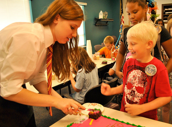 Samantha Eichelberger (left) cuts cake for Owen McGinnis (center, 8), both of Elburn, while Kiara Scott (10) of North Aurora waits for hers. The cake was part of the Town and Country Public Library's birthday party for Harry Potter Tuesday afternoon.