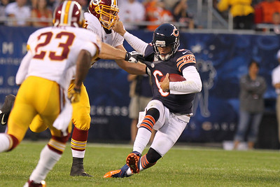 Mike Greene - mgreene@shawmedia.com Bears quarterback Jay Cutler holds onto a defender while scrambling during a preseason game against the Washington Redskins Saturday, August 18, 2012 at Soldier Field in Chicago.