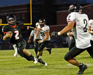Brett Moist / For the Northwest Herald Crystal Lake Central Quarterback Kyle Lavand tries to run past Huntley's Mike Andrews (2) and Marcus Wright II during the second quarter at Crystal Lake Central High School on Friday.