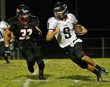 Brett Moist / For the Northwest Herald Huntley Quarterback Kameron Sallee tries to outrun Crystal Lake Central's Josh Mugler during the second quarter at Crystal Lake Central High School on Friday.