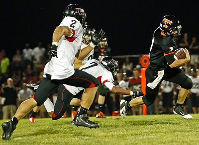 Brett Moist / For the Northwest Herald Crystal Lake Central Quarterback Kyle Lavand scrambles past Huntley's Mike Andrews (front), Damario Hughes (middle), and Mitchell Kawell (back) during the third quarter at Crystal Lake Central High School on Friday.