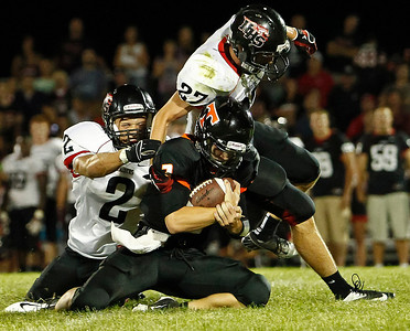 Brett Moist / For the Northwest Herald Huntley's Mike Andrews (left) and Josh Sepsey tackle Crystal Lake Central Quarterback Kyle Lavand during the third quarter at Crystal Lake Central High School on Friday.