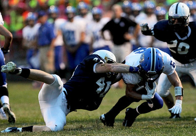 Sarah Nader - snader@shawmedia.com Cary-Grove's Brock Bussenger (left) tackles Sean Lynch during the third quarter of Friday's game in Cary on August 31, 2012. Cary-Grove won, 21-6.