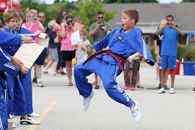 Mike Greene - mgreene@shawmedia.com Chul Lee's Martial Arts Academy member Jakub Rugalo, 11 of Cary, jumps to hit a board during a demonstration at SportsFest 2012 Sunday, August 19, 2012 in Cary. The annual sports and fitness showcase, sponsored by the Cary Grove Area Chamber of Commerce, featured over 50 area vendors and demonstrations throughout the event from local groups.