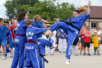 Mike Greene - mgreene@shawmedia.com Chul Lee's Martial Arts Academy member Colleen Fletcher, 15 of Cary, breaks a series of boards with a kick during a demonstration at SportsFest 2012 Sunday, August 19, 2012 in Cary. The annual sports and fitness showcase, sponsored by the Cary Grove Area Chamber of Commerce, featured over 50 area vendors and demonstrations throughout the event from local groups.