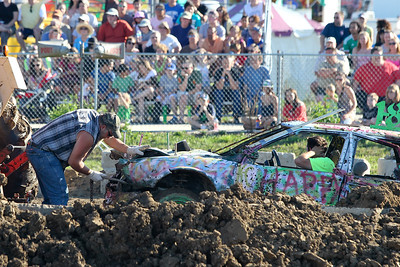 Mike Greene - mgreene@shawmedia.com Crew members haul away the 18 car driven by Scott Redden, of Woodstock, after the compact heat of the the Demoliton Derby competition at the McHenry County Fair Sunday, August 5, 2012 in Woodstock.