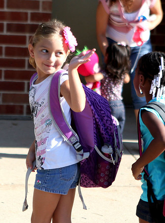 First-grader Alyssa Bandur waves to her mom as she heads into the building for her first day of school at Fox Ridge Elementary School in St. Charles Wednesday morning.