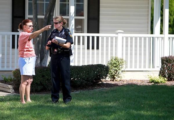 Neighbor Diane Henry talks with a Geneva police officer as firefighters investigate house fire in the 2000 block of Sheffield Lane in Geneva. (Sandy Bressner photo)
