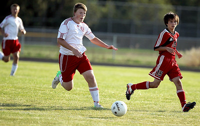Sarah Nader - snader@shawmedia.com Marian Central's Ryan Przbysz (center) kicks the ball down field during  the first half of Thursday's game against Huntley in Woodstock on Thursday, August 23, 2012.