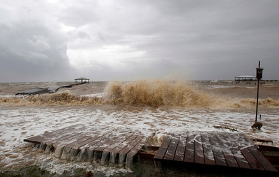 Waves tear apart a pier along Mobile Bay near Dauphin Island on Tuesday, August 28, 2012 in Coden, Ala. Alabama took a glancing blow from Hurricane Isaac on Tuesday as it headed toward landfall in the northwestern Gulf of Mexico, but the storm still threatened the coast with high winds, torrential rain and pounding surf. (AP Photo/Butch Dill)