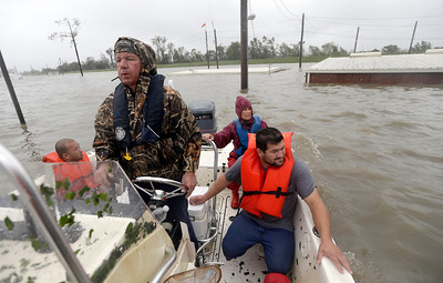 Lanny LaFrance, left, drives his boat while rescuing flood people from their flooded home as Hurricane Isaac hit Wednesday, Aug. 29, 2012, in Braithwaite, La. (AP Photo/David J. Phillip)