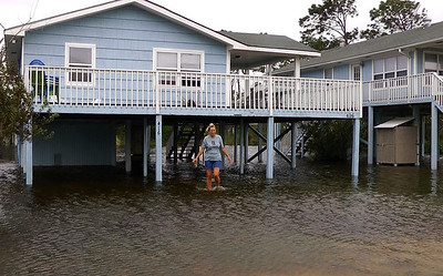 Gina Johnson wades through her front yard in Gulf Shores, Ala., on Wednesday, Aug. 29, 2012, after the coastal town took a glancing blow from Hurricane Isaac as it made landfall in Louisiana. While the storm brought heavy rain and wind to the Alabama coast, little significant damage was reported. (AP Photo/Jay Reeves)