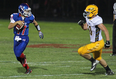 H. Rick Bamman - hbamman@shawmedia.com Jacobs'Adam Kulon (right) chases down Marmion's Brock Krueger for a loss Friday during the second quarter of the season opener Friday in Aurora.