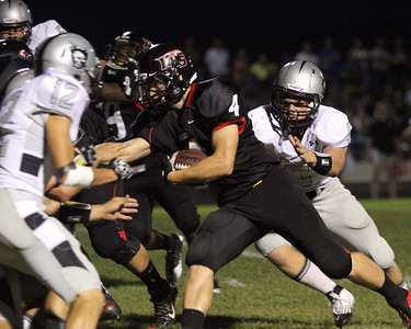 Don Lansu / For the Northwest Herald Huntley running back Ethan Connor (4) picks up short yardage before being brought down by Kaneland defenders Gary  Koehring (5) and John Pruett (12)in the second quarter in Huntley