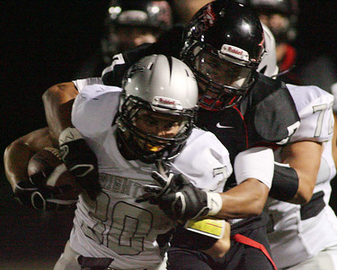 Don Lansu / For the Northwest Herald Kaneland running back (30) Jesse Balluff is brought down by Huntley defensive back Damario Hughes (7) after a short gain during first quarter action at Huntley.