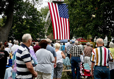 "Josh Peckler - Jpeckler@shawmedia.com People turn towards a giant American flag that was hanging from a Mchenry Fire Department ladder truck during a ""Keep The Spirit of '45 Alive"" Day event held at Veterans Memorial Park in Mchenry Sunday, August 12, 2012. The event honored World War II veterans who live in the Mchenry County area."