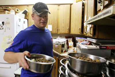 Mike Greene - mgreene@shawmedia.com Jason Waters, of Cary, works preparing meals for some of the 58 dogs  displaced by Hurricane Isaac that were taken in by Lucky-E Kennel Thurday, August 30, 2012 at the kennel in Ringwood. The kennel is currently looking for support boarding some of the animals as well as donations to help aid their efforts.