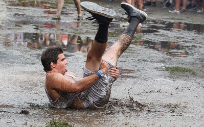 Sarah Nader - snader@shawmedia.com Concert goers  slide in the mud after a rain storm flooded Grant Park  during day two at Lollapalooza in Chicago on Saturday, August 4, 2012.