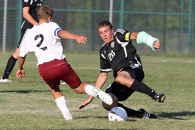 Mike Greene - mgreene@shawmedia.com Marengo's Jake Piske (left) attempts to kick a ball as Kaneland's Alec Koczka slides to hit it during a game Tuesday, August 21, 2012 at Marengo High School. Kaneland defeated Marengo 4-1.