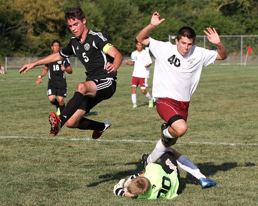 Mike Greene - mgreene@shawmedia.com Kaneland's Anthony Parillo (left) and Marengo's Jordan Herrera jump over Marengo goalkeeper Dylan Marks during a game Tuesday, August 21, 2012 at Marengo High School. Kaneland defeated Marengo 4-1.