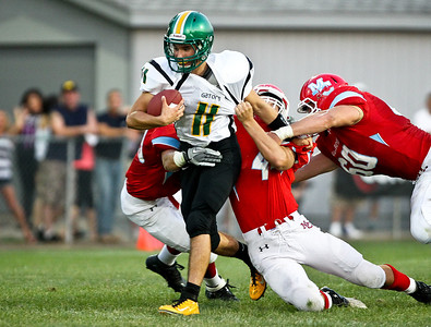 Josh Peckler - Jpeckler@shawmedia.com Crystal Lake South's Greg Galloway (11) tries to escape Marian Central defenders Thomas Lesniewski (44) and Christian Scroggs (60) during the second quarter at Marian Central Catholic High School Friday, August 24, 2012.