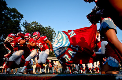 Josh Peckler - Jpeckler@shawmedia.com Members of Marian Central's football team break through a banner as they enter the field for a game against Crystal Lake South at Marian Central High School Friday, August 24 2012.