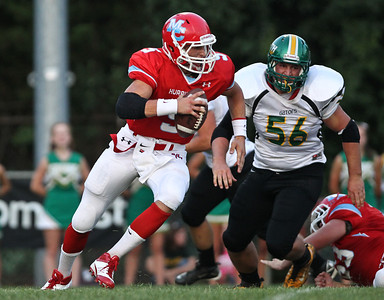 Josh Peckler - Jpeckler@shawmedia.com Marian Central quarterback Chris Streveler (5) is chased by Crystal Lake South's Nick Amren (56) during the first quarter at Marian Central Catholic High School Friday, August 24, 2012.