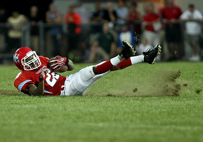 Josh Peckler - Jpeckler@shawmedia.com Marian Central's Ephraim Lee looses his footing on the grass during a run while playing Crystal Lake South at Marian Central High School Friday, August 24 2012.