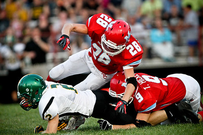 Josh Peckler - Jpeckler@shawmedia.com Marian Central's Ryan Hickey (28) and Tyler Hickey (9) tackle Crystal Lake South's Lake Larson during the first quarter against Crystal Lake South at Marian Central Catholic High School Friday, August 24, 2012.