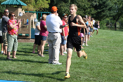Mike Greene - mgreene@shawmedia.com Crystal Lake Central's Alex Bake crosses the finish line of the boys 3 mile competition during a McHenry County Cross Country Meet Saturday, August 25, 2012 at McHenry Township Park in Johnsburg. Baker took first place in the competition.