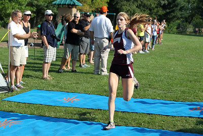 Mike Greene - mgreene@shawmedia.com Marengo's Katie Adams crosses the finish line in first place in the girls 3 mile competition during a McHenry County Cross Country Meet Saturday, August 25, 2012 at McHenry Township Park in Johnsburg.