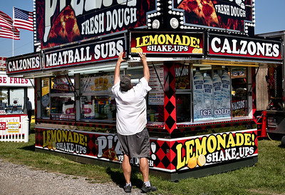 Josh Peckler - Jpeckler@shawmedia.com A vendor fixes a lemonade sign on his food stand as he prepares for customers during the McHenry County Fair Wednesday, August 1, 2012.