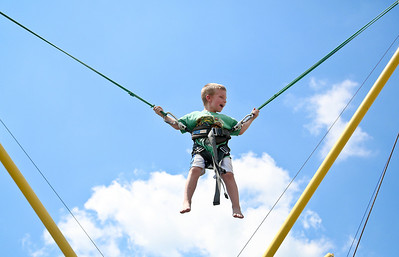 Josh Peckler - Jpeckler@shawmedia.com Gavin Hauck, 4 of Johnsburg lets out a smile as he flies through the air on a bungee jump trampoline during the McHenry County Fair Wednesday, August 1, 2012.