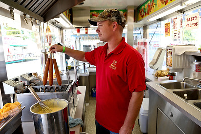 Josh Peckler - Jpeckler@shawmedia.com Casey Glass of Hughes Springs, Tex. pulls out corn dogs from a deep fryer as he prepares for customers during the McHenry County Fair Wednesday, August 1, 2012.