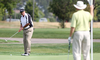 Mike Greene - mgreene@shawmedia.com Tom Cisar prepares to putt on the 1st green as Eric Mayer tends the flag during the first day of the the McHenry County Senior Amateur tournament Wednesday, August 15, 2012 at Whisper Creek Golf Club in Huntley.