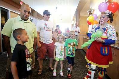 Mike Greene - mgreene@shawmedia.com Casey Lechuga, 6 of Carpentersville, waits with his dad Fred for a balloon from Lollypop the Clown during a grand opening event for the Randall Oaks Recreational Center Saturday, August 25, 2012 in West Dundee. The event included tours, demonstrations, crafts, games, and contests for all ages.