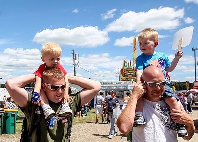 Sarah Nader - snader@shawmedia.com Aaron Krejci (left) of Woodstock and Jeremy Brokaw of Woodstock carry their sons, Cayden Krejci (left), 2, and Jay Brokaw, 2, while walking around the McHenry County Fair in Woodstock Saturday, August 3, 2013.
