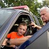 Elburn Police Chief Steve Smith shows 7-year-old Connor Anderson different aspects of a police squad car during Elburn's National Night Out event at Lions Park Tuesday.
