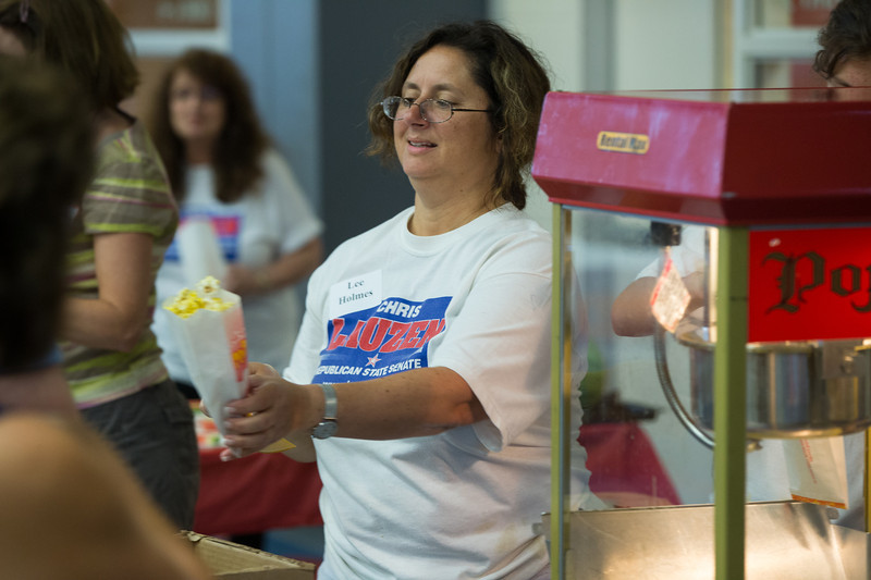 Volunteer Lee Holmes of St. Charles passes out popcorn during the 19th Annual Porky Picnic at The Vaughan Athletic Center in Aurora, IL on Saturday, August 10, 2013 (Sean King for Shaw Media)