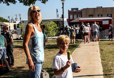 Sarah Nader -  snader@shawmedia.com Stacy Ormsby (left) of Crystal Lake and her son, Ethan, 7, walk around the farmers market after buying a pickle of a stick at Summer Field's pickle stand during the Crystal Lake farmers market at Depot Park Saturday, August 24, 2013.