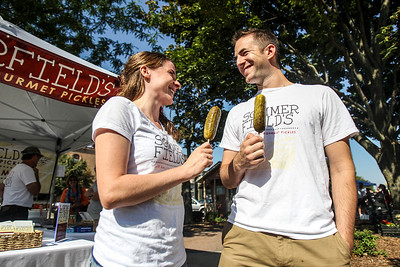 Sarah Nader -  snader@shawmedia.com Madison Sommerfield (left) and her husband, Matt Sommerfield of Crystal Lake pose for a portrait at their pickle stand at the Crystal Lake farmers market Saturday, August 24, 20013.