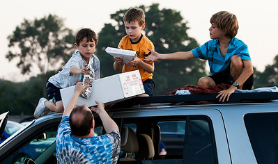 Kyle Grillot - kgrillot@shawmedia.com   Steven Schaffer hands food to his sons Logan Schaffer, 8, Justin Schaffer, 6, and Mason Argabright, 10, during Super Hero Night at the McHenry Outdoor Theater Saturday, August 24, 2013. More than a dozen superheroes from the Costumers with a Cause gather to raise money for the drive-in theater.