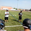 St. Charles North defensive line coach Dan Meyo (left) and Head Coach Rob Pomazak (right) address the team during practice Thursday. Meyo is a former assistant coach at Elk Grove High School, where Pomazak also coached.
