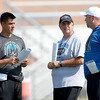 St. Charles North Head Coach Rob Pomazak (left) talks with defensive line coach Dan Meyo (center) and special teams coach Tom Poulin during practice Thursday. Meyo is a former assistant coach at Elk Grove High School, where Pomazak also coached.