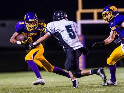 Kyle Grillot - kgrillot@shawmedia.com   Woodstock North senior Jake Schnulle (5) goes to tackle Waconda junior Josh Anderson (3) during the second quarter of the high school football game at Wauconda High School Friday, August 30, 2013.