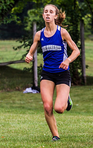 Kyle Grillot - kgrillot@shawmedia.com   Woodstock senior Maura Beattie finishes the 3-mile race during the McHenry County Cross Country meet at the McHenry Township Park Saturday, August 31, 2013. Beattie came in first with a time of 17:52.5.