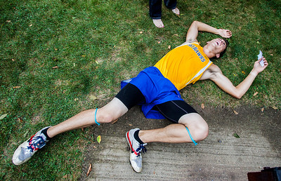 """Kyle Grillot - kgrillot@shawmedia.com   Johnsburg junior Noah Miller collapses after the 3-mile race during the McHenry County Cross Country meet at the McHenry Township Park Saturday, August 31, 2013. Miller finished 17th with a time of 17:13. """"It's hard work, but its rewarding"""" Miller said, """"it's definitely rewarding."""""""